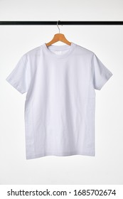 Blank White T-Shirt Mock-up hanging on white background.