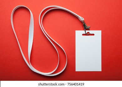 Blank white vertical badge mockup, isolated on red background. Name tag on neck. Person identity label.