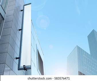 Blank white vertical banner on building facade, design mockup. Store flag mock up on the street. Outdoor banneret template on the side of the shop exterior. Sign hanging on the wall.