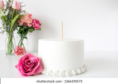 Blank white wedding cake with pink flowers and stick for topper, mother's day mock up