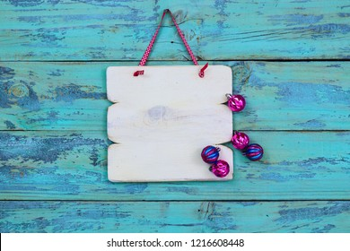 Blank white wood sign hanging by ribbon on antique rustic teal blue wood door with pink and turquoise Christmas ornaments; holiday background with aged painted copy space