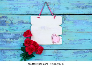 Blank white wood sign with pink hearts and red roses hanging on rustic teal blue wood door; Valentines Day holiday background