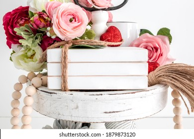 Blank white wooden book stack decor on tier tray with flowers, valentinen's day mockup - Shutterstock ID 1879873120