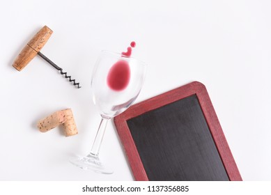 Blank Wine Menu: Chalkboard with wine glass, corkscrew, corks, and wine spill on white with copy space.