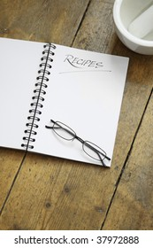 A blank wire spiral bound recipe book with the title 'recipe' hand written at the top of the page. A pair of black framed glasses rest on the page. Set on a wooden kitchen table top.