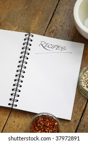 A blank wire spiral bound recipe book with the title 'recipe' hand written at the top of the page. Set on a wooden kitchen table top. Glass dishes of dried chillies and dried white beans also visible.