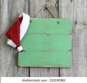 Blank wood holiday sign with Christmas Santa Claus hat hanging on antique rustic wooden background; Christmas background with green copy space