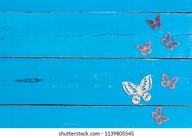 Blank wood sign with butterflies border and antique rustic teal blue wooden background; family, home, nature concept with copy space