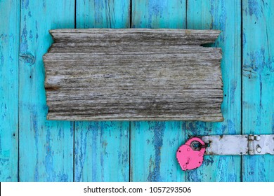 Blank wood sign by pink antique padlock hanging on rustic teal blue wooden door; message board background with love and home concept and copy space