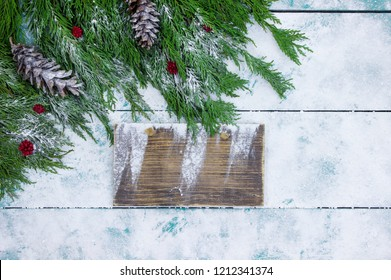 Blank wood sign with Christmas tree garland border, red berries and pine cones on antique rustic wooden snowy background; winter holiday sign with decorations and copy space