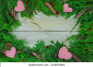 Blank wood sign with Christmas tree garland border with hearts, candy canes and pine cones; holiday background with copy space