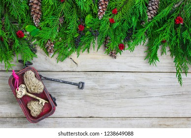 Blank wood sign with Christmas tree garland border with pine cones and red wagon with key and hearts; holiday background with copy space