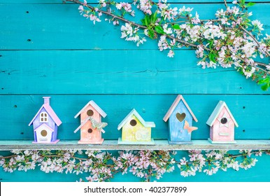 Blank wood  sign with colorful birdhouses with butterfly on shelf by spring tree flowers on antique rustic teal blue wooden background; pink, purple, yellow and orange birdhouses