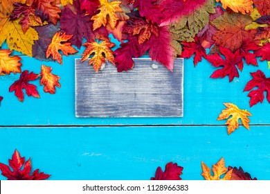 Blank wood sign with colorful fall leaves border and antique rustic teal blue wooden background; autumn, Thanksgiving, Halloween, seasonal nature background with copy space