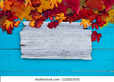 Blank wood sign with colorful fall leaves border hanging on antique rustic teal blue wooden background; autumn, Thanksgiving, Halloween, seasonal nature sign with copy space