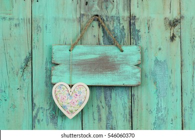 Blank wood sign with country fabric pink floral heart hanging on antique rustic mint green wooden background; holiday background with painted  copy space