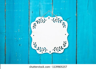 Blank wood sign with floral border hanging on antique rustic teal blue wooden door; message board with copy space