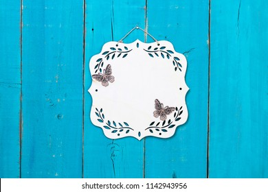 Blank wood sign with floral border and butterflies hanging on antique rustic teal blue wooden door; family, home, love concept background with white copy space