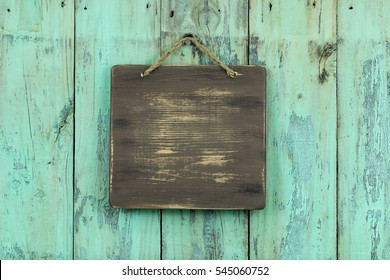Blank wood sign hanging by rope on antique rustic shabby mint green wooden background; empty sign with painted copy space