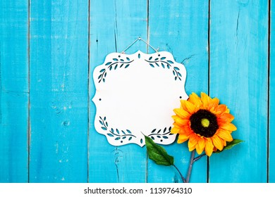 Blank wood sign with orange, yellow and red flower hanging on antique rustic teal blue wooden door; springtime, Mothers Day, autumn, Memorial Day holiday background with copy space