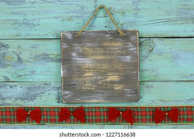 Blank wood sign with red Christmas bow and plaid ribbon border hanging on antique rustic teal blue wooden door; holiday background with painted copy space