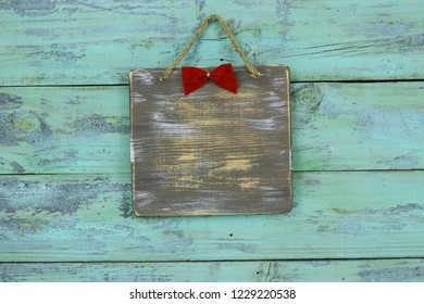Blank wood sign with red Christmas bow hanging on antique rustic teal blue wooden door; holiday background with painted copy space