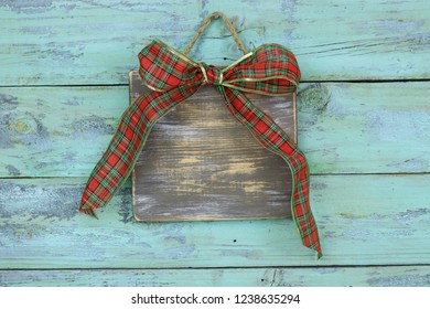 Blank wood sign with red and green plaid Christmas bow hanging on antique rustic teal blue wooden door; holiday background with aged copy space