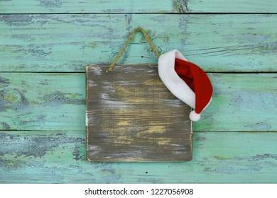 Blank wood sign with red and white Christmas Santa Claus hat hanging on antique rustic teal blue wooden door; holiday background with painted copy space