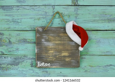 Blank wood sign with red and white Christmas Santa Claus hat and the word Believe hanging on antique rustic teal blue wooden door; holiday background with painted copy space