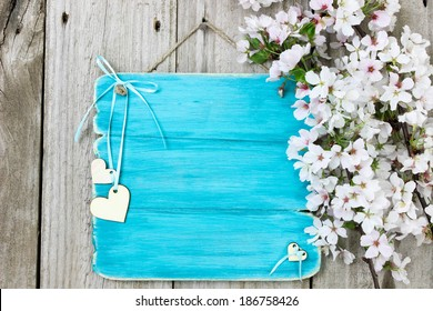 Blank wood sign with white spring flowers and wooden hearts hanging on antique rustic wood background; teal blue copy space background