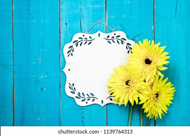 Blank wood sign with yellow flowers hanging on antique rustic teal blue wooden door; springtime, Mothers Day, autumn, Memorial Day holiday background with copy space