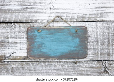 Blank wood teal blue sign hanging on antique rustic white wooden background; painted background with copy space