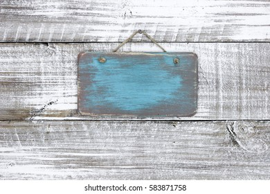 Blank wood teal blue sign hanging by rope on antique rustic white wooden background; painted background with copy space