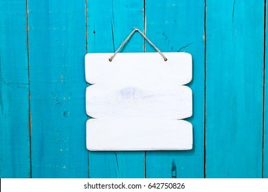 Blank wood white sign hanging by rope on antique rustic teal blue wooden background; painted background with copy space