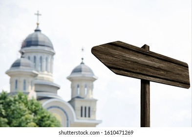 Blank wooden arrow sign outside pointing to a big city church cathedral with urban view in the background. Empty advertising arrow signage outdoors with copy space for your text image or design