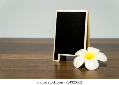 Blank wooden black board with white plumeria flower
