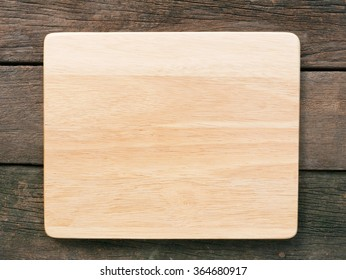 The blank wooden board on the old deep brown planks background.