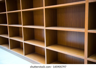 Blank wooden bookshelf in a library.