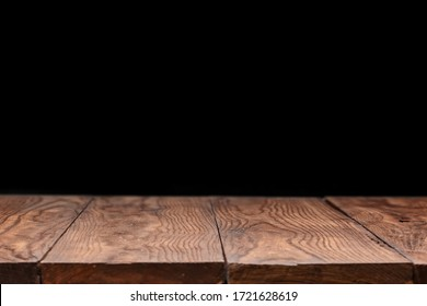Blank wooden deck table against black wallpaper background for present product and other things. Can be used for your creativity.