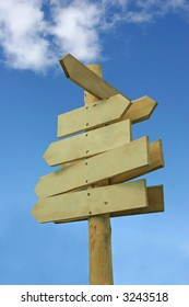 Blank wooden direction signpost against a blue sky