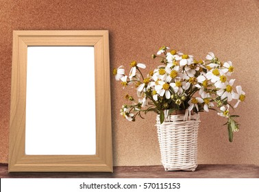 blank wooden frame mockup with basket of chamomile flowers on wooden table and brown paper wall in vintage tone.