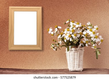 blank wooden frame mockup with basket of chamomile flowers and cactus on wooden table and brown paper wall in vintage tone.