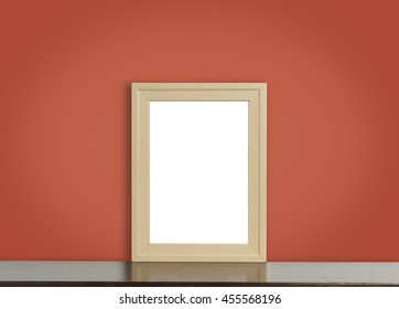 Blank wooden photo frame on rustic red background.