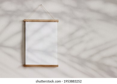 Blank wooden picture frame hanging on beige wall. Empty poster mockup for art display in sunlight. Minimal interior design.Palm leaves shadow overlay. Summer design. Copy space. No people.