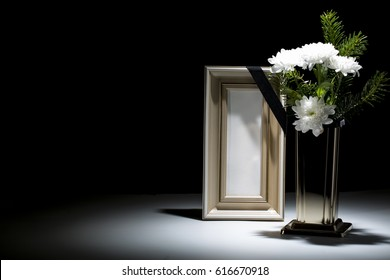 blank wooden picture frame, with vase and flower on dark background