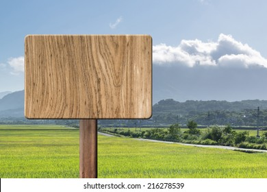 Blank wooden sign on field of farm. Concept of rural, idyllic, tranquility etc.