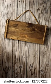 blank wooden signboard on aged wooden wall