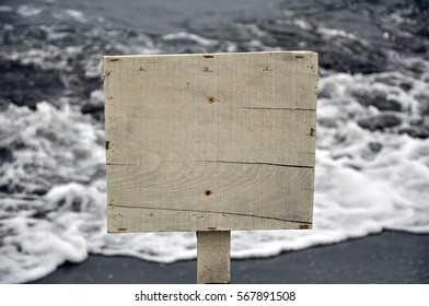 Blank wooden signboard ,sea waves on background