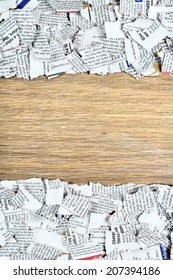 Blank wooden surface and shredded newspaper pieces on top and bottom.