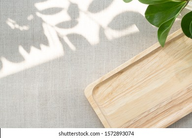 A blank wooden tray neatly arranging on linen table cloth, with the space show sunlight and beautiful leaves shadow. Background with copy space for natural and minimal products. Soft and calm concept